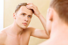 Topless man fixing hair in front of mirror Royalty Free Stock Photography