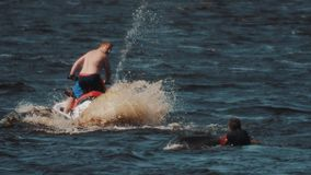 Topless man on jet ski rides around surfer, who floats in water with wakeboard stock video footage