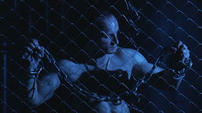 Topless man with metal chain beyond the fence stock footage