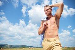 Topless man outdoor with hand in hair looks away Stock Photos