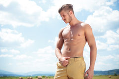 Topless man outdoor with hand on pants looks down. Young topless man posing outdoor with hand on pants and looking down, away from the camera Stock Photo