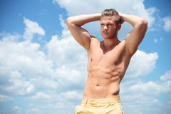 Topless man outdoor with hands at back of head. Young topless man posing outdoor with his hands at the back of his head while looking away Stock Photo