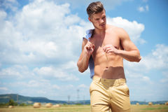 Topless man outdoor looks down with straw in hand Stock Photo