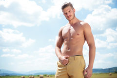 Topless man outdoor looks at you with hand on pants Stock Images