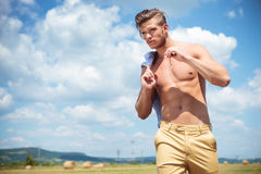 Topless man outdoor walks with straw in hand Stock Photography