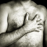 Topless man suffering a pain in his chest Stock Images
