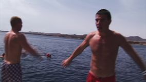 Topless men jump into water from yacht. Vacation. Flips. Sunny day. Splash. stock video