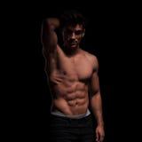 Topless, muscular man raising his arm Stock Photos