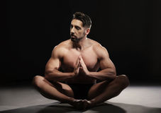 Topless Muscular Man Sitting in a Yoga Position Stock Photo