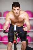 Topless Muscular Man Spinning Gym Bike Stock Image