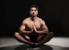 Topless muskulöst mansammanträde i en yogaposition royaltyfria bilder
