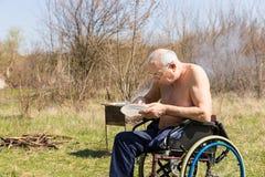 Topless rörelsehindrad gamal man som äter på parkera bara Arkivbild