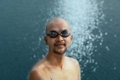 Topless swimming bald beard man in black goggle portrait with white light bokeh blue sea water background. Topless swimming bald beard man in black goggle stock photo