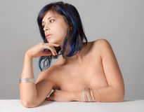 Topless Woman With Bracelets. A portrait of a pretty woman wearing silver bracelets and leaning on a white table Stock Photos