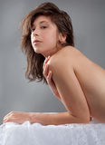 Topless Woman Leaning on Table. An image of an  attractive young woman leaning on a table covered in lacy white fabric Stock Photos