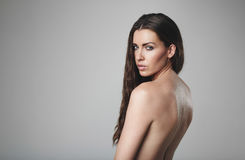 Topless woman looking at you. Naked female model posing on grey background. Topless caucasian woman looking at you Stock Image