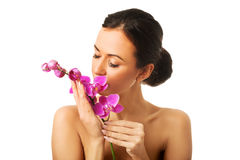 Topless woman with purple orchid branch Stock Image