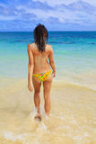 Topless woman walks into the ocean. Beautiful young woman in a yellow bikini at the beach at lanikai walking topless into the ocean to wash off the beach sand Stock Photography