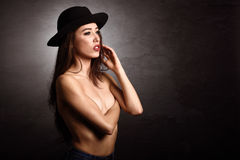 Topless woman wearing blue jeans, panties and hat Royalty Free Stock Image