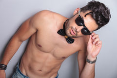 Topless young man holds his sunglasses Stock Photos