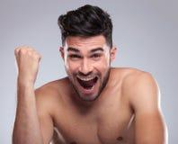 Topless young man screaming of joy. Winning in studio Stock Image