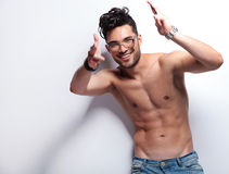 Topless young man shoots you with hands. Young topless man shooting with his bare hands and smiling at the camera. on light gray background Stock Photo