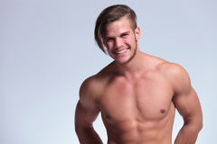 Topless young man shows a big smile. Young topless man with lean body showing a big smile and revealing braces. on gray background Royalty Free Stock Photography