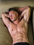 Topless young man on sofa. Shirtless sexy young man in panties relaxing on couch and looking away. From above Royalty Free Stock Image