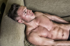 Topless young man on sofa Royalty Free Stock Images