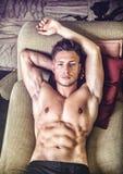 Topless young man on sofa Stock Photos