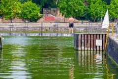 Topless young man standing on swimming docks at Shadwell Basin i Stock Images