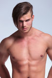 Topless young man stands with hands at back. Cutout picture of a young topless man standing with his hands at his back and looking at the camera. on gray Stock Images