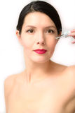 Topless young woman holding a dropper. Low angle view of a beautiful topless young woman holding a dropper filled with eye drops or anti-age serum in her hand Royalty Free Stock Image