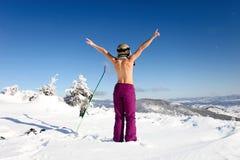 Toplesse Stellung des weiblichen Skifahrers auf der Ferse eine Rückseite Lizenzfreie Stockfotos