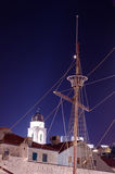 Topmast and cables of an old ship from the time of the discoveries against a clear bell tower at night. Royalty Free Stock Photography