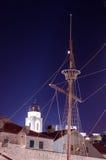 Topmast e cabos de um navio velho da época das descobertas contra uma torre de sino clara na noite fotografia de stock royalty free