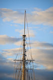 Topmast. Of the 75-foot gaff rigged schooner Mary E. at sunset as a cool weather front sweeps gray and white clouds across a blue sky Stock Photography