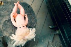 Topo de madeira com uma boneca plástica imagens de stock royalty free