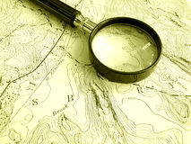 Topographic map with magnifier. An image showing a topographical map - a land plan with hills, mountains, valley, river, lakes and other topographic features