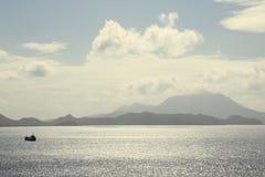 Topographie St. Kitts entlang Küste mit dem kleinen Boot angesehen vom Ozean an einem sonnigen Tag der Bucht Lizenzfreies Stockfoto