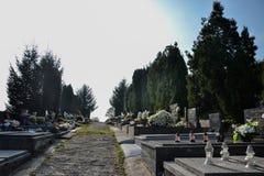 TOPOLCANY,斯洛伐克- 30 10 2015年:坟墓、墓碑和耶稣受难象在传统公墓 奉献的蜡烛灯笼和花 库存图片