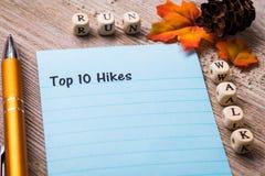 Topp 10 listar nedgångvandringar begrepp på anteckningsboken och träbräde Arkivbild