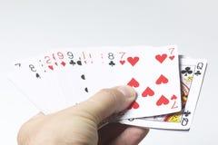 topp- modig lycka för kort fyra Mannen rymmer ut en packe av kort På en vit bakgrund Royaltyfri Bild