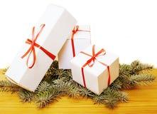 Toppa dei contenitori di regalo di bianco con i regali rossi dei chistmass del nastro che aspettano su alto vicino di legno e del Fotografia Stock