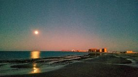Toppen måne över Rocky Point At Dawn Arkivbild