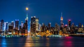 Toppen måne ovanför New York horisont arkivbild