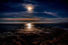 Toppen måneinställning på stranden arkivbild