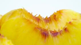 Toppen makroskytte av mogna persikaavsnitt Långsamt rotera på skivtallriken som isoleras på den vita bakgrunden arkivfilmer