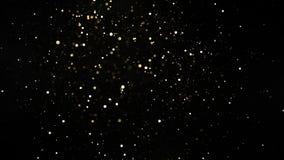 Toppen ultrarapid av att blänka guld- partiklar på svart bakgrund, låg dof stock video