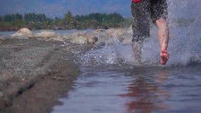 Toppen ultrarapid sköt av okänd manspring på grunt vatten in mot kamera stock video